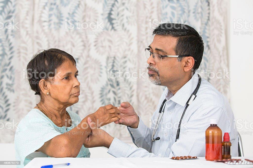 Mature Doctor examining a Rheumatoid Arthritis patient stock photo