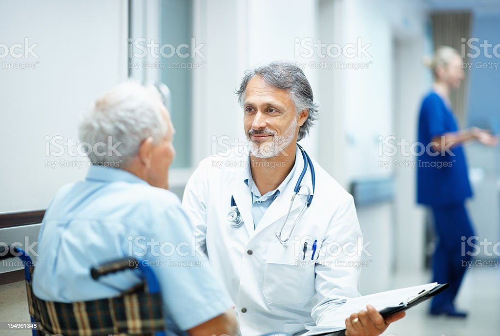 Mature doctor explaining reports to a handicapped man royalty-free stock photo