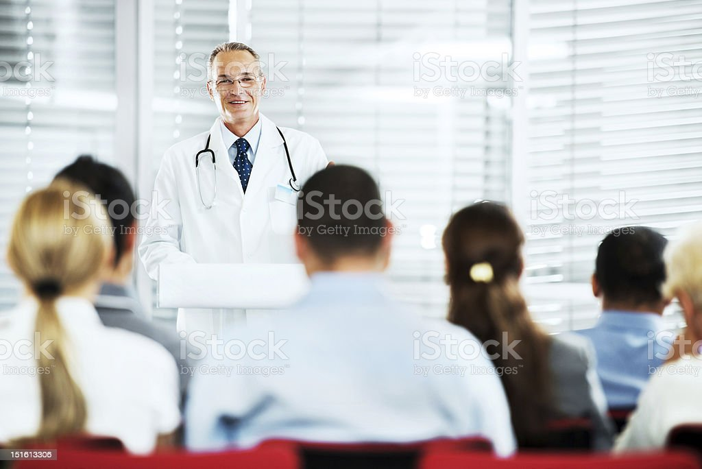 Mature doctor giving a speech on  seminar. stock photo
