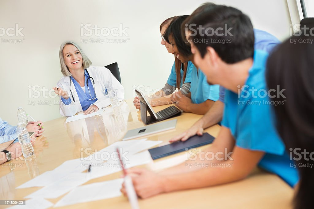 Mature doctor having meeting with hospital staff in board room royalty-free stock photo