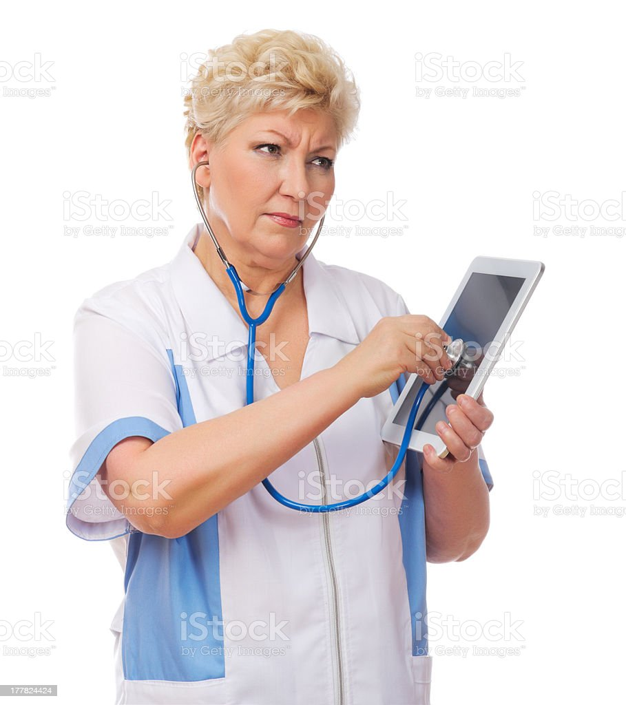 Mature doctor listen tablet PC by stethoscope royalty-free stock photo