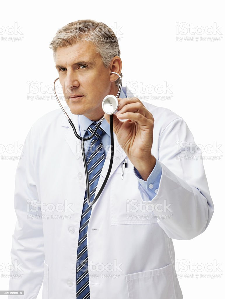 Mature Doctor Listening To Heartbeat Through Stethoscope stock photo