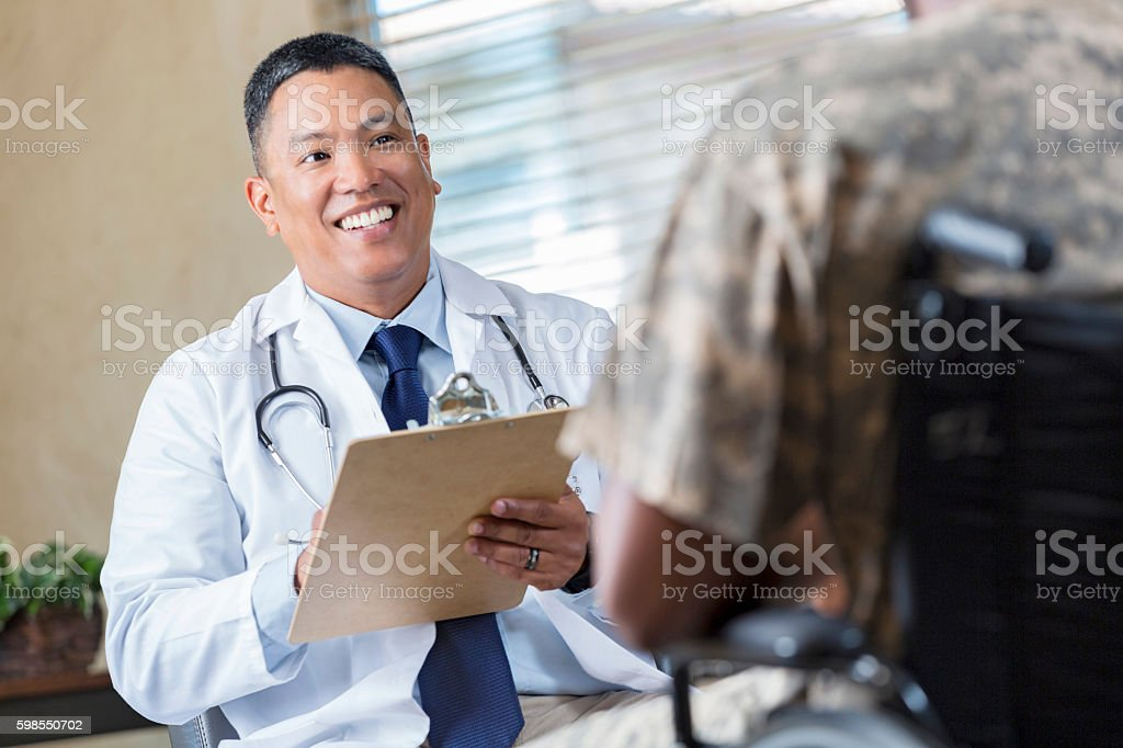 Mature doctor meeting with injured solider in veteran's hospital stock photo
