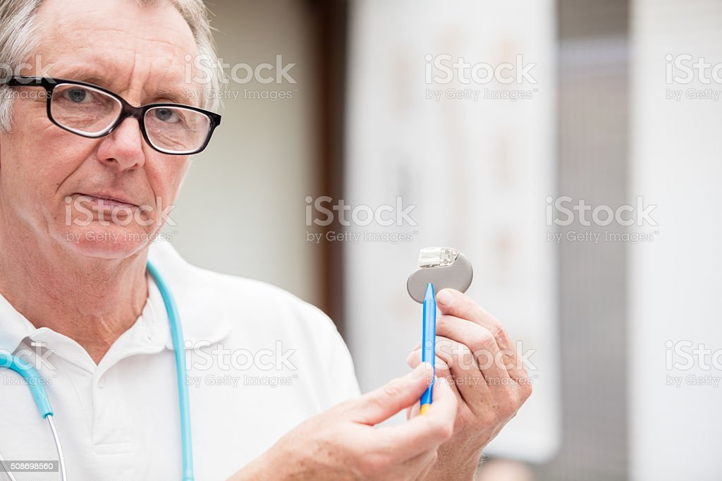 Mature doctor pointing at a cardial pacemaker stock photo