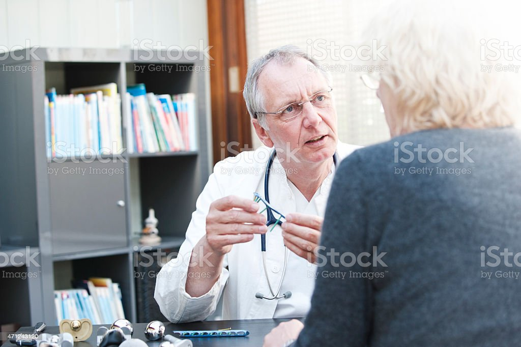 Mature doctor presenting humerus plate to female patient stock photo