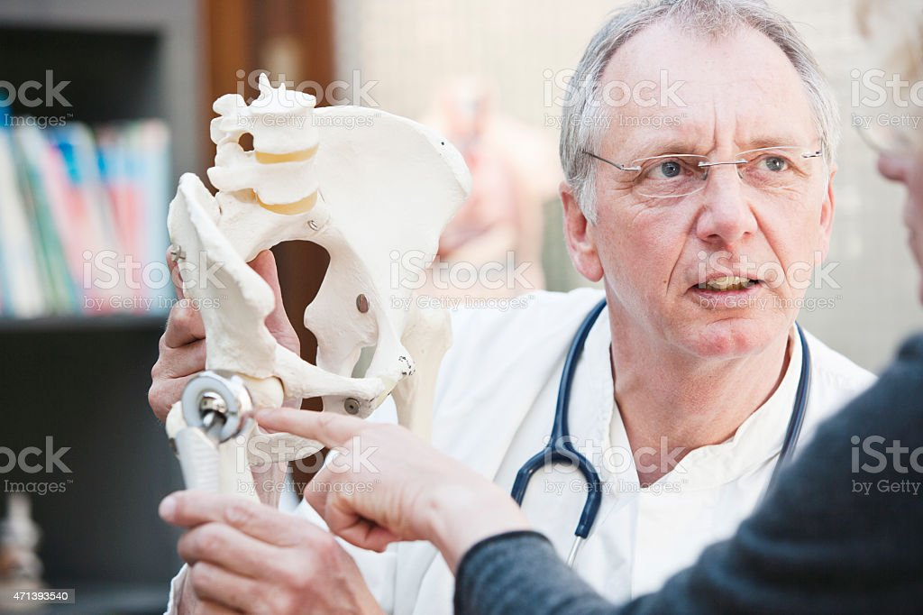 Mature doctor presenting total hip arthroplasty to female patient stock photo