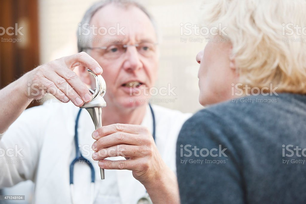 Mature doctor presenting total knee arthroplasty to female patient stock photo