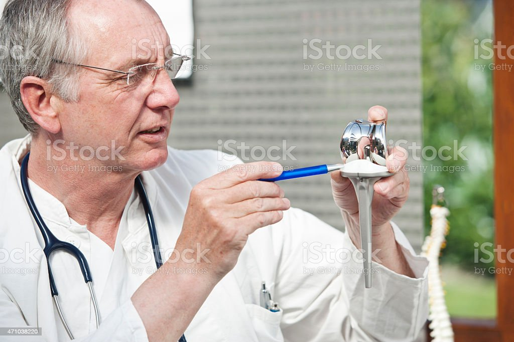 Mature doctor presenting total knee prosthesis and pointing on inlay stock photo