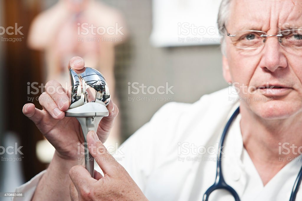Mature doctor presenting total knee prosthesis stock photo