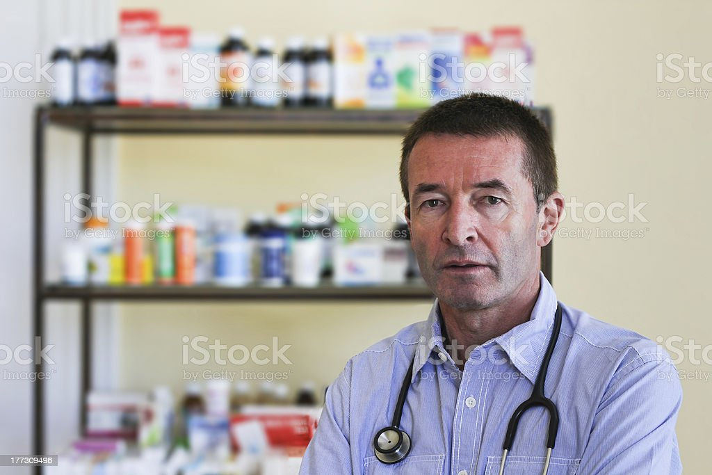 Mature Doctor Standing In Front Of Medicine royalty-free stock photo