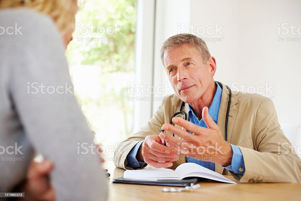 Mature doctor talking with his female patient sitting at desk royalty-free stock photo