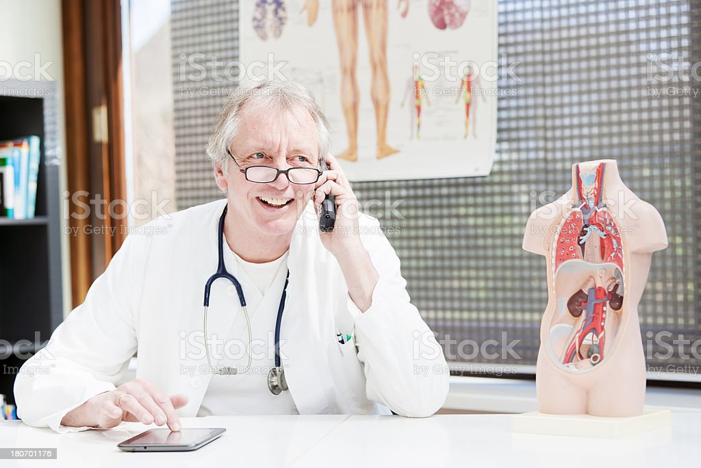 Mature doctor telephoning stock photo