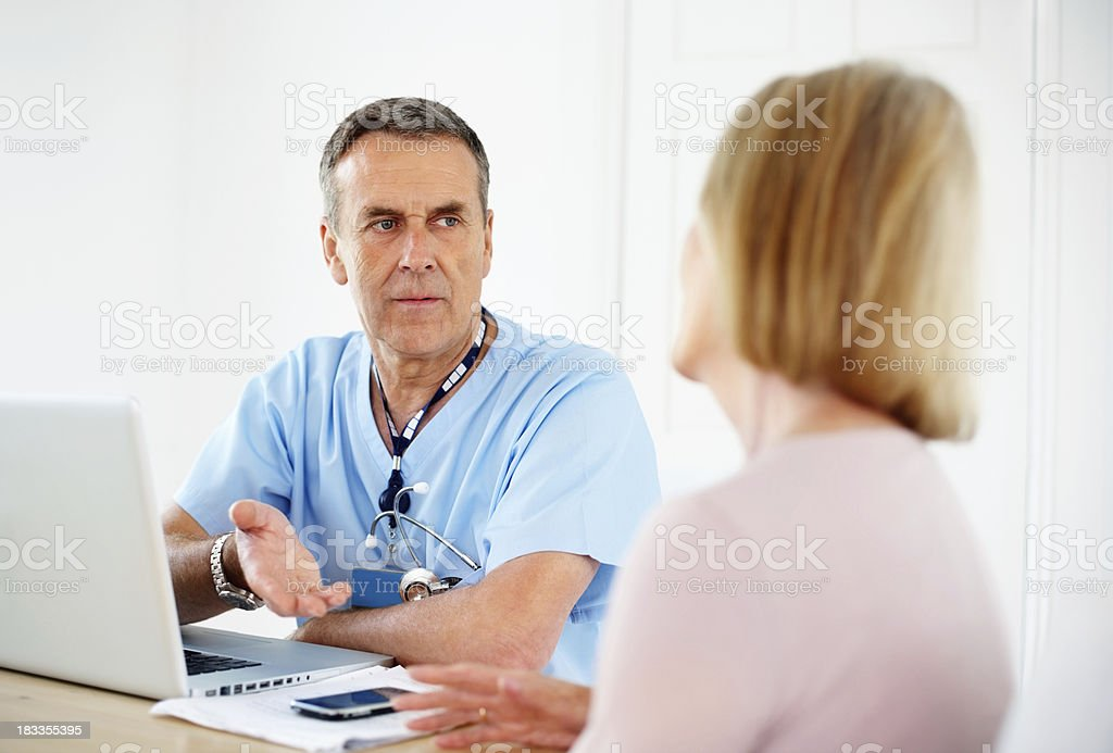 Mature doctor with laptop on desk consulting female patient royalty-free stock photo