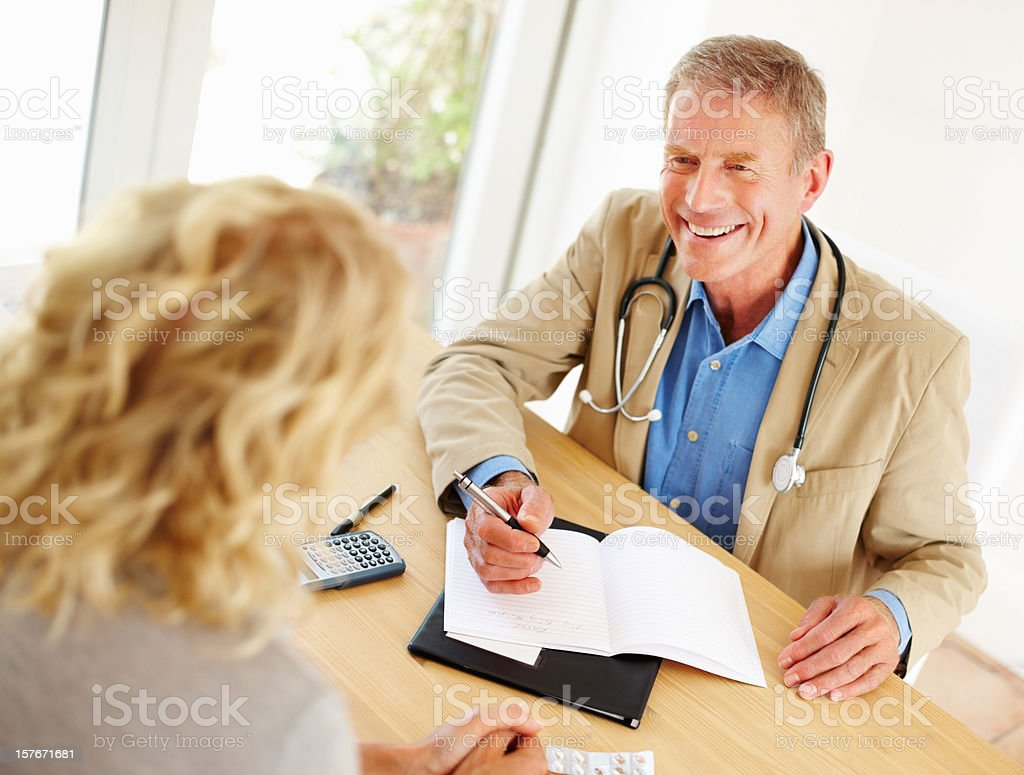 Mature doctor writing a prescription in front of female patient royalty-free stock photo