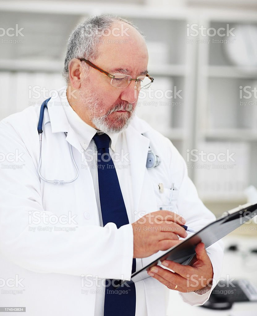 Mature doctor writing reports royalty-free stock photo