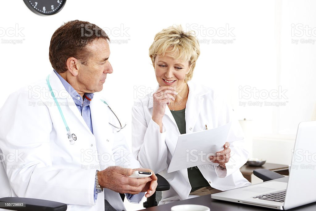 Mature doctors sitting at desk in office royalty-free stock photo