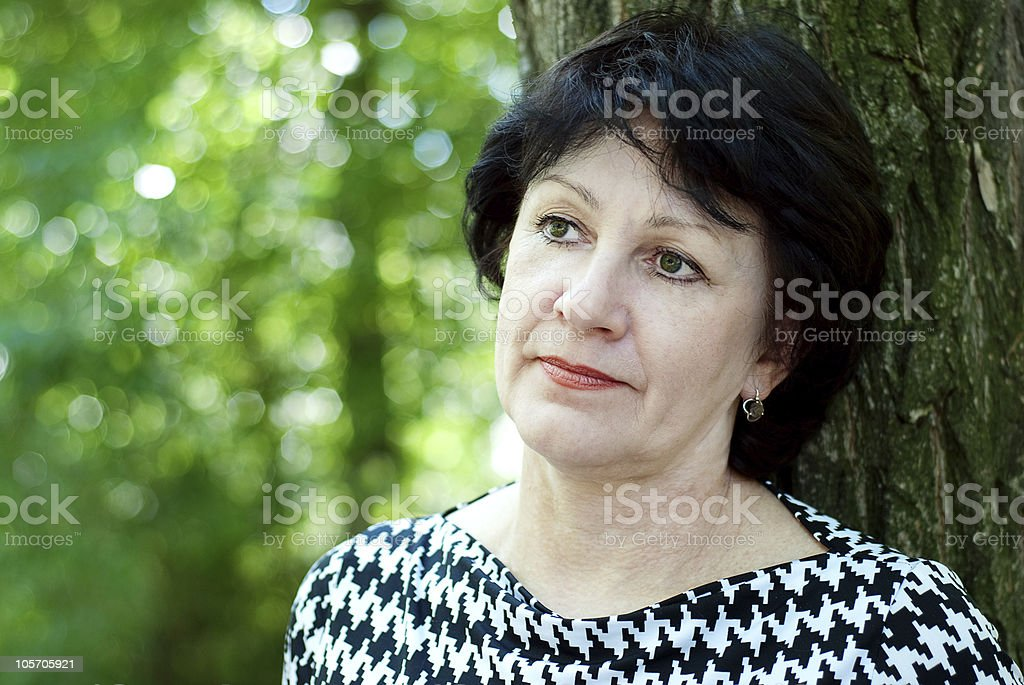 Mature dreamy woman in the park royalty-free stock photo