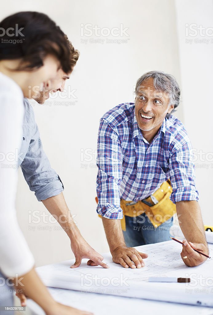 Mature engineer discussing plans with young couple royalty-free stock photo