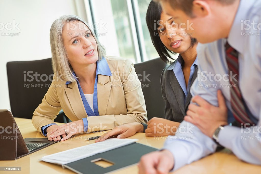 Mature executive having discussion with colleagues in board room meeting royalty-free stock photo