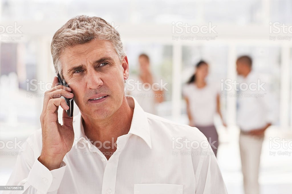 Mature executive using cellphone with colleagues behind him royalty-free stock photo