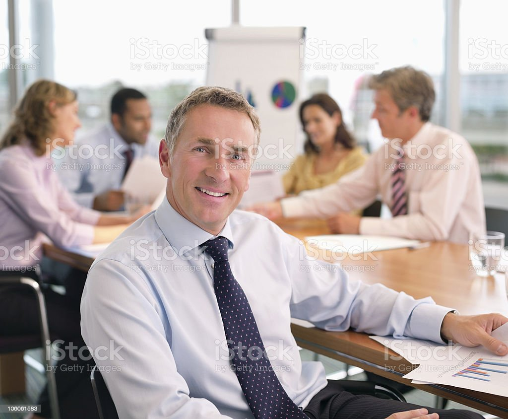 Mature executive with colleagues discussing at conference table in the background royalty-free stock photo