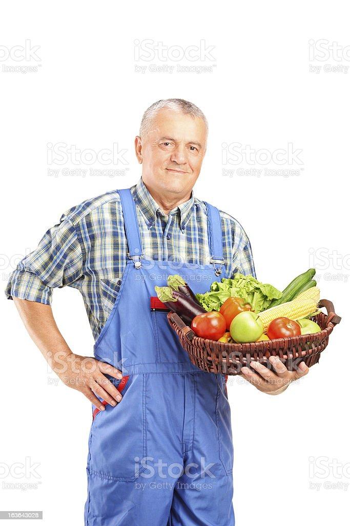 Mature farmer holding a basket full of vegetables stock photo