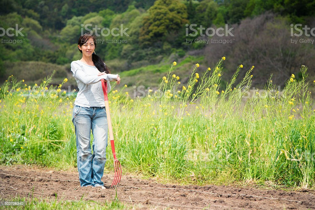 Mature farmer stood in a field leaning on a pitchfork stock photo
