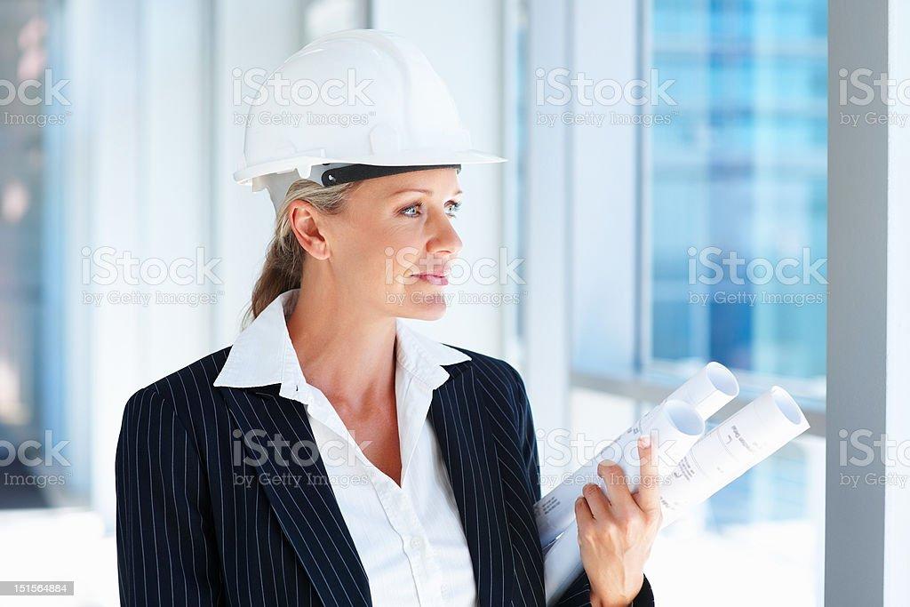 Mature female architect holding blueprints royalty-free stock photo