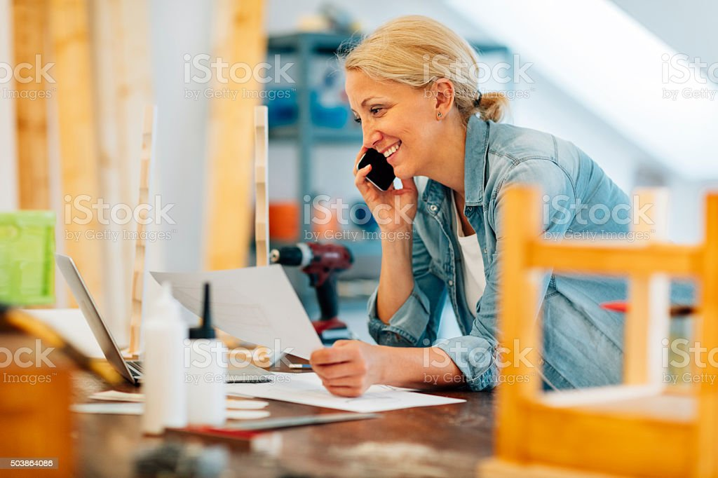 Mature female carpenter on the phone stock photo