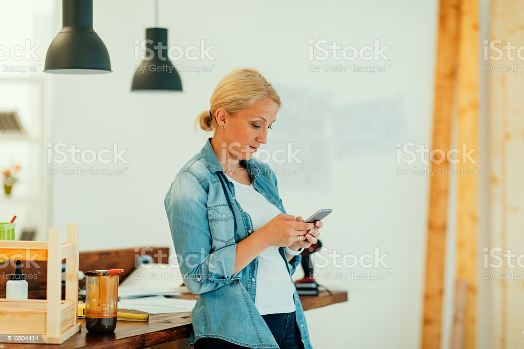 Mature female carpenter typing message stock photo