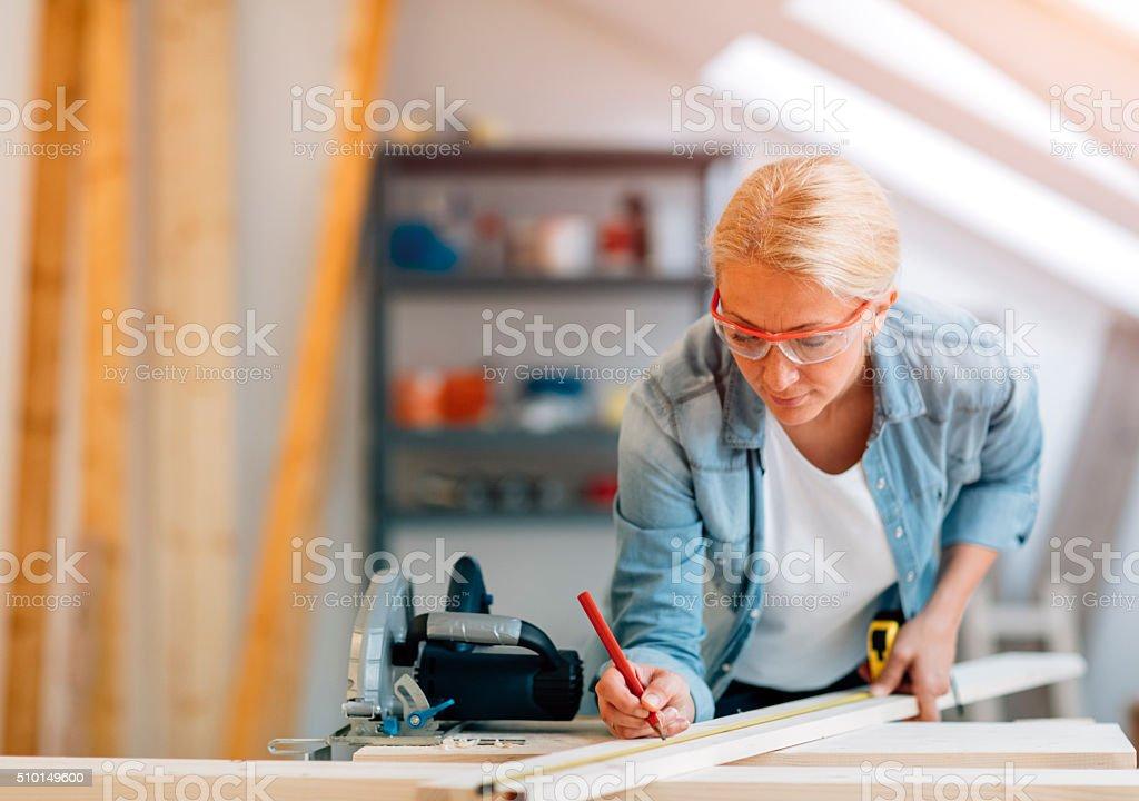 Mature female carpenter working in her workshop stock photo