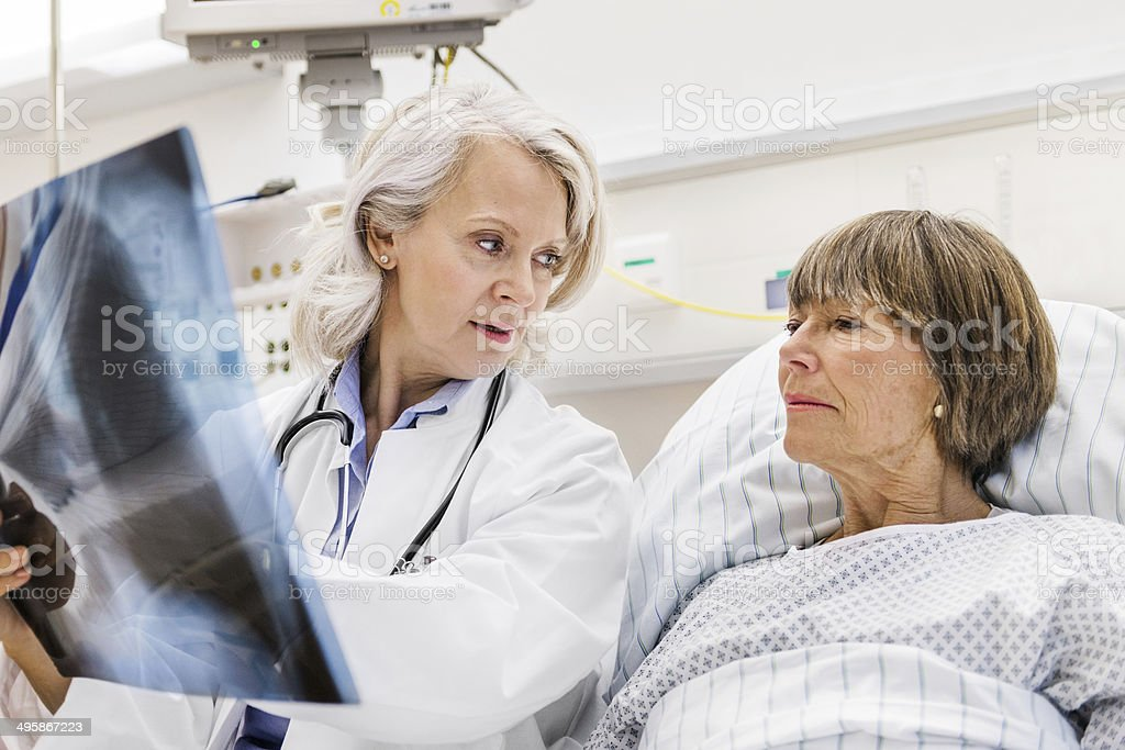 Mature Female Doctor Checking X-Ray With Mature Patient stock photo