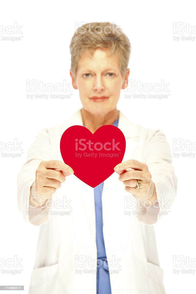 Mature female doctor holding red heart to camera royalty-free stock photo