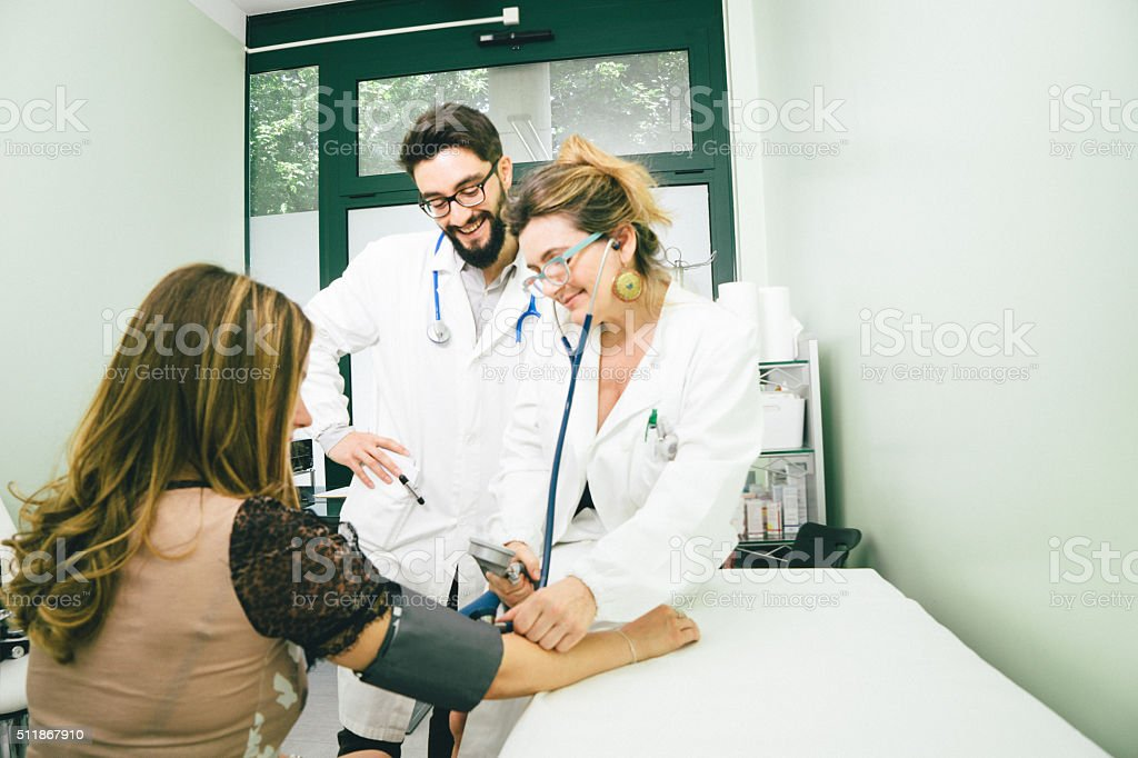 Mature Female Doctor Measuring Blood Pressure stock photo