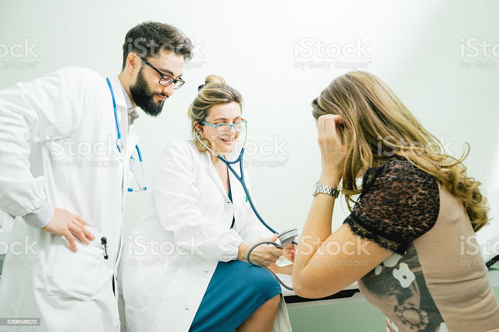 Mature Female Doctor Measuring Blood Pressure stock photo