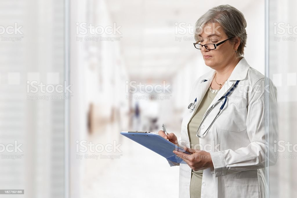 Mature female doctor on hospital corridor royalty-free stock photo