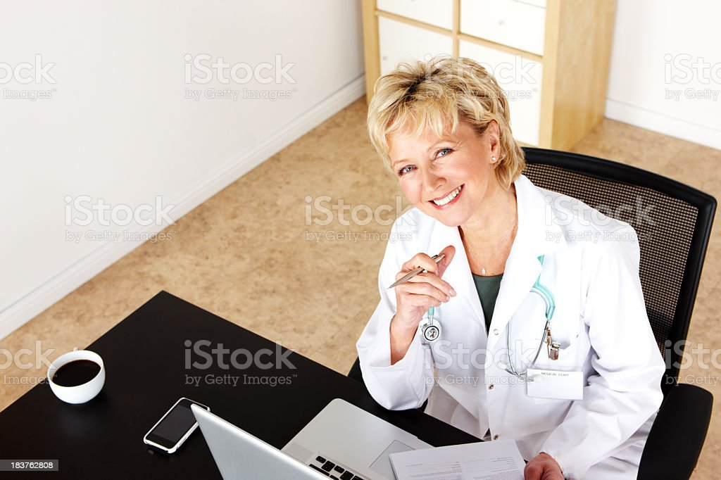 Mature female doctor sitting at desk in office royalty-free stock photo