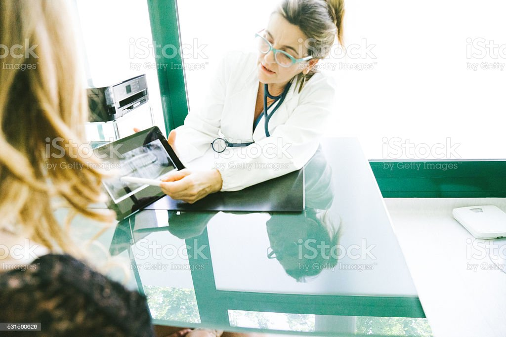 Mature Female Doctor Using A Digital Tablet For His Diagnosis. stock photo
