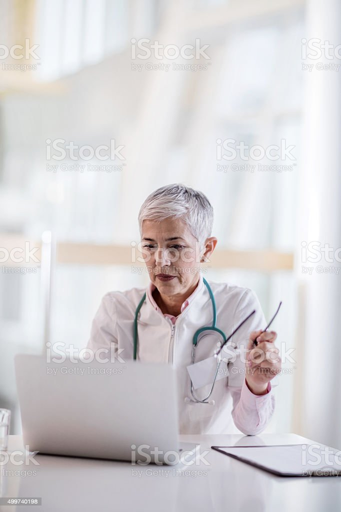 Mature female doctor working on laptop in the office. stock photo