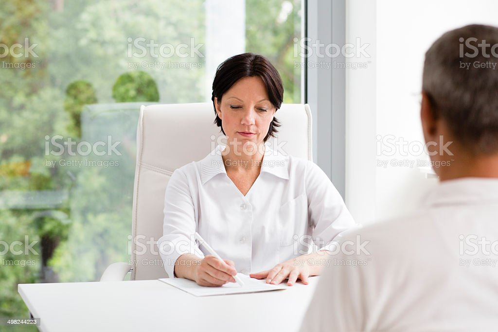 mature female doctor writes down the diagnosis. royalty-free stock photo