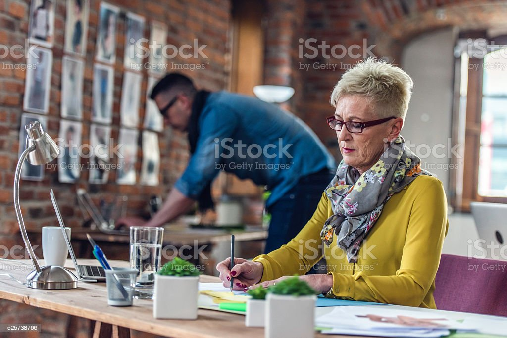 Mature female executive writing behind a desk in the office stock photo