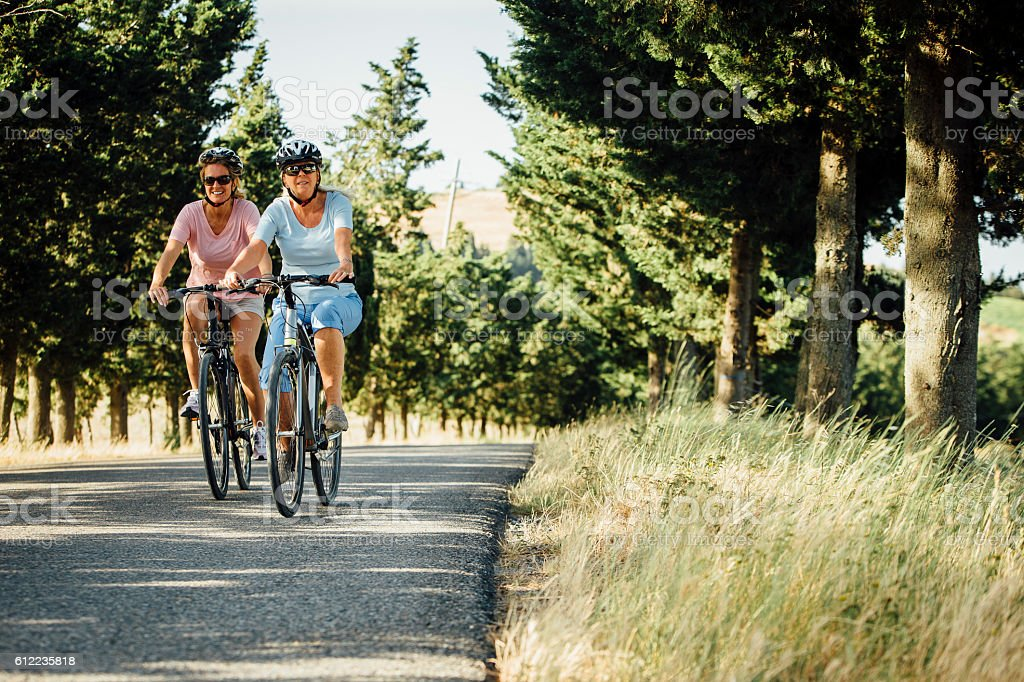 Mature Female Friends Cycling in Tuscany stock photo