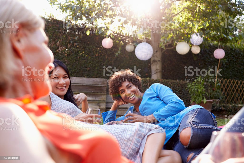 Mature Female Friends Enjoying Drinks In Backyard Together royalty-free stock photo