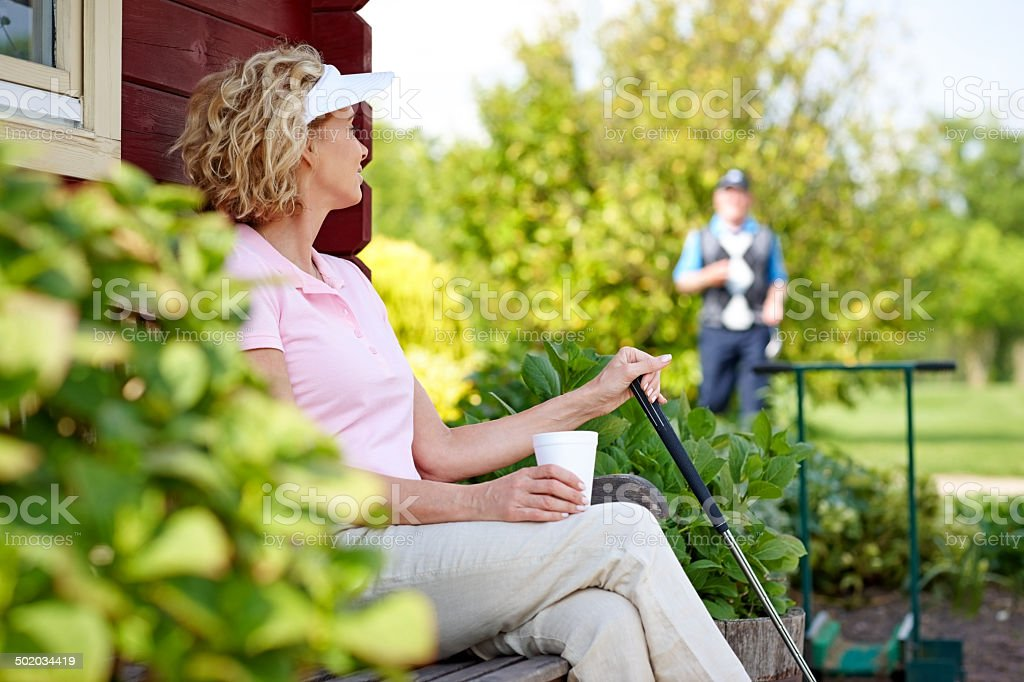 Mature female golfer relaxing after a game stock photo
