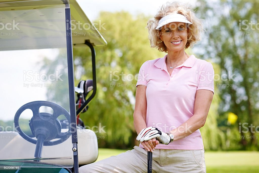 Mature female golfer standing with her golf cart stock photo