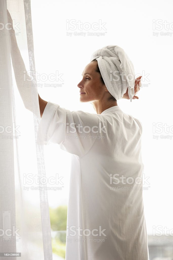 Mature female in bathrobe relaxing by the window stock photo