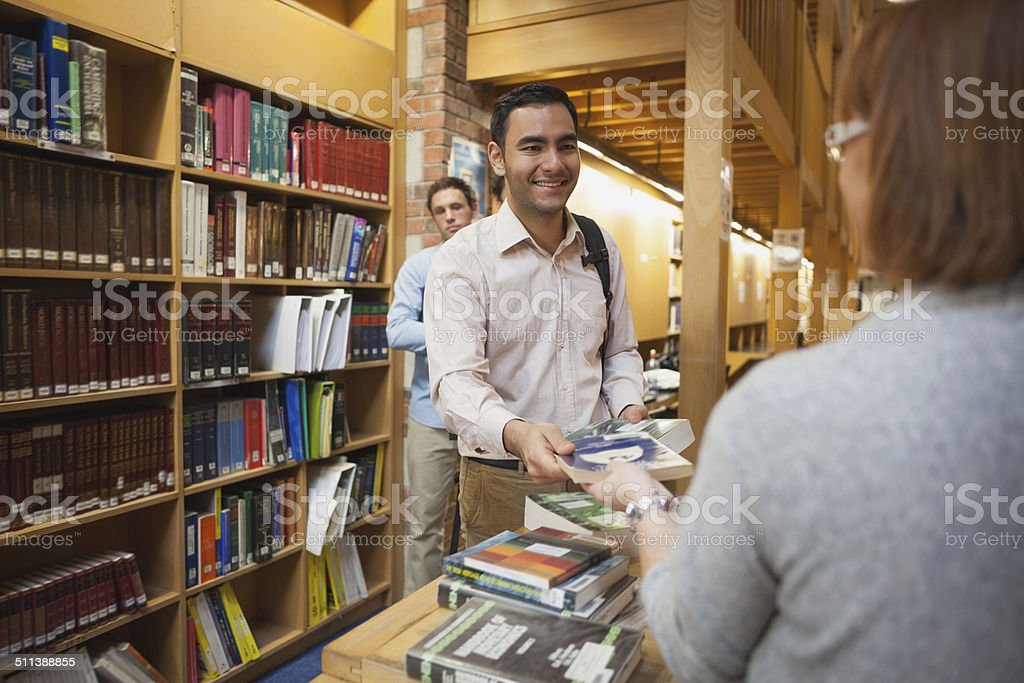 Mature female librarian handing a book to young man stock photo