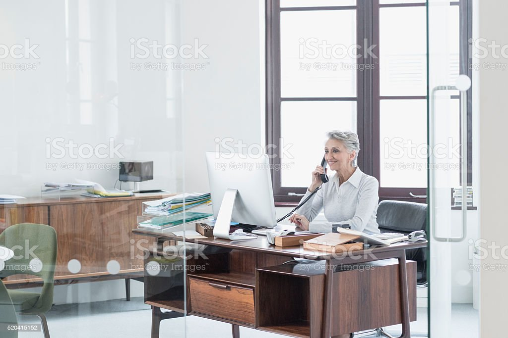 Mature female manager on the phone in office stock photo