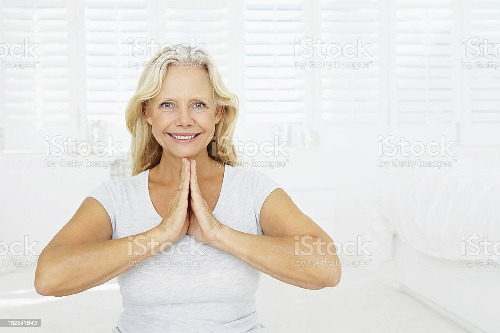 Mature female meditating in bed at home royalty-free stock photo