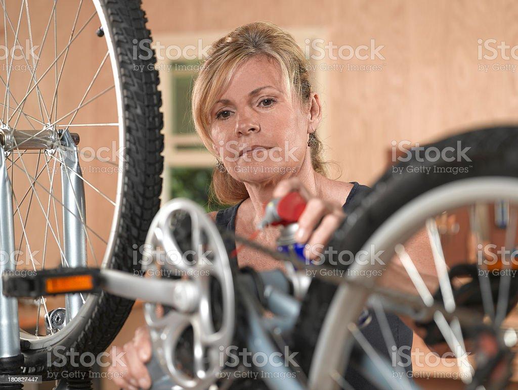 Mature Female oiling Bike chain royalty-free stock photo